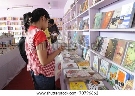 KOLKATA- FEBRUARY 4: Young adults flip through books during the 2011 Kolkata Book Fair in Kolkata, India on February 4, 2011.
