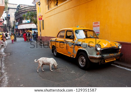 KOLKATA, INDIA - JAN 12: Antique yellow color  taxi cab stoped on a narrow street with pedestrians on January 12, 2013 in Kolkata, India. The car is Hindustan Ambassador, manufactured since 1958