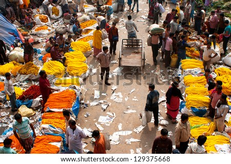 KOLKATA, INDIA - JAN 11: Crowd of people buy & sell flowers in Mullik Ghat Flower Market on January 11, 2013. The market is more than 125 years old. More than 2000 sellers work in the market every day