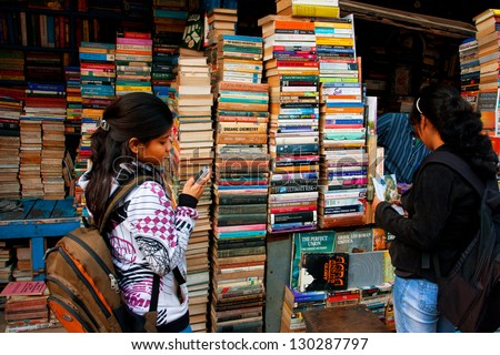 KOLKATA, INDIA - JAN 15: Young female student with a cell phone choose the book on the street market on January 15, 2012 in Kolkata. From 1976 Kolkata have the Book Fair with 2 million visitors annual