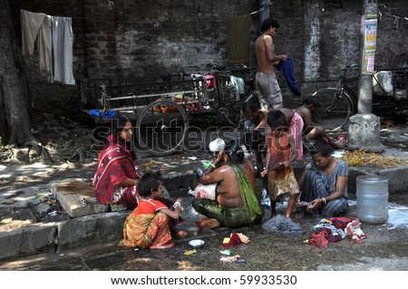 KOLKATA, INDIA - OCTOBER 27:Local people wash themselves on the street of Kolkata on October 27, 2009.  Homeless living on the street are common in every city of India.