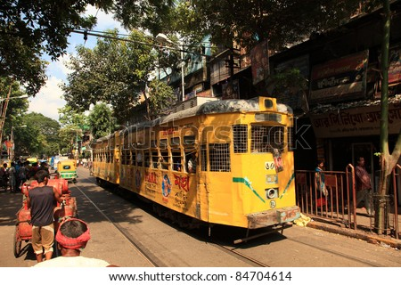 KOLKATA - OCTOBER 20: A yellow colored tram runs through the crowded streets of Kolkata on October 20, 2010 in Kolkata, India. Kolkata is the only city in India having tram transportation network.