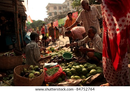 KOLKATA - OCTOBER 17: Customers buy vegetables from a street vendor in a busy road on October 17, 2010 in Kolkata, India. Its a common practice in India to sell vegetables in open markets and streets.
