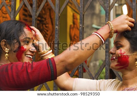 KOLKATA - OCTOBER 10: Two Women devotees applies sindhoor on each other head during Durga Puja festival on October 10, 2011 in Kolkata, India.