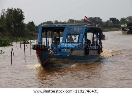 KOMPONG KLEANG, CAMBODIA - FEB 12, 2015 - Tourist boat travels along the waterway of Kompong Kleang floating fishing village,  Cambodia