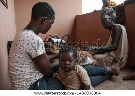 Kongo Village / Ghana - 02.24.2015: Ghanaian woman with a young child and her mother making famous Bolgatanga market baskets out of elephant grass (veta vera) #1486006004