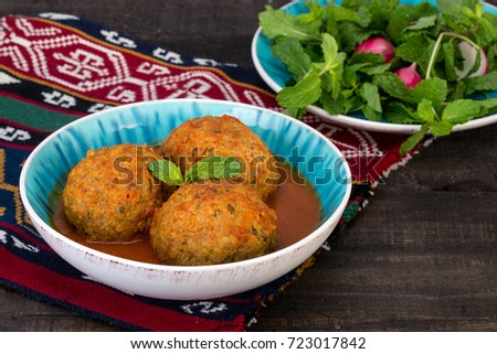 Koofteh Tabrizi Large Meatballs Stuffed With Dried Fruits, Berries And Nuts In Tomato Turmeric Broth A Traditional Azeri And Iranian Dish Served In Turquoise Bowl and Herbs