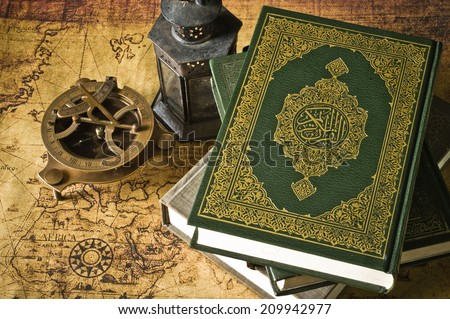 Koran holy book of Muslims with lantern and compass the old map