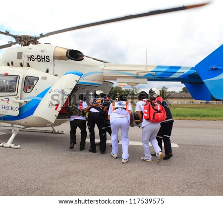 KORAT, THAILAND - SEP 15 : Bangkok Hospital Rescue team(white) pulling cart with wounded person to helicopter in Search and Rescue Exercise(SAREX) on September 15, 2012 in Nakhonratchasima,Thailand