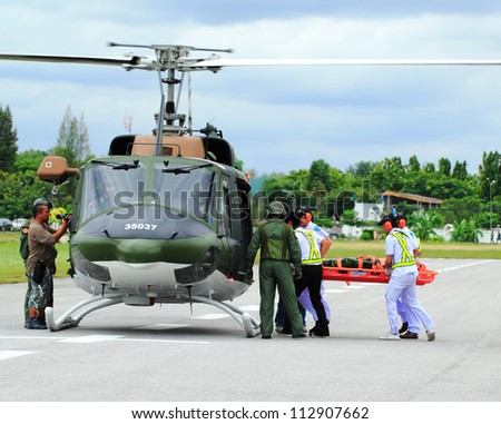 KORAT, THAILAND - SEP 15 : Military Rescue Team(white) pulling cart with wounded person to helicopter in Search and Rescue Exercise(SAREX) on September 15, 2012 in Nakhonratchasima,Thailand