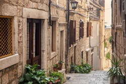 Korcula old narrow Mediterranean street with stairs. Rough stone houses, facades with windows, green plants, flowers in Dalmatia, Croatia. Historical place creating a picturesque and idyllic scenery