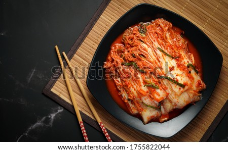 Korea food top view, Chinese cabbage kimchi in black dish set on dark background.