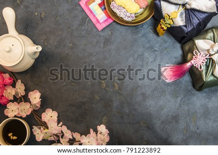 Korea traditional object on the blue paper. cherry blossom. lucky bag, wrapped present, cookies, tea