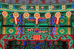 Korean architecture - colorful wooden roof of gazebo painted in traditional Korean floral style.