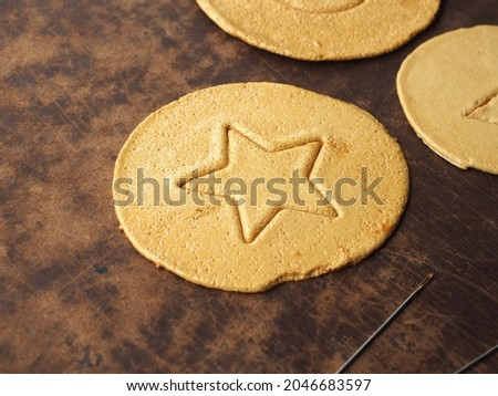 Korean Dalgona or Ppopgi candy game, honeycomb toffee sugar candy with star shape on wooden board