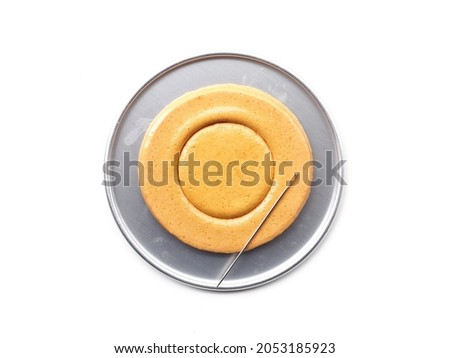Korean Dalgona or Ppopgi honeycomb sugar candy with circle shape and needle in round tin tray on white background