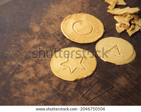 Korean Dalgona or Ppopgi honeycomb toffee sugar candy with star, circle and triangle pattern on brown wooden board with needle