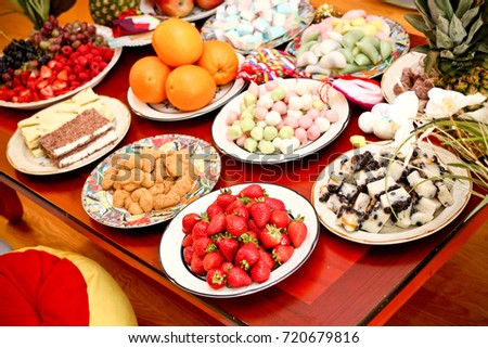 Korean dessert table at a dinner party with strawberries, oranges and a variety of colorfully decorated rice cakes #720679816