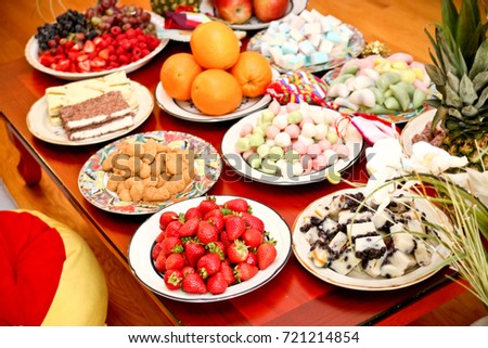 Korean dessert table at a dinner party with strawberries, oranges and a variety of delicious rice cakes #721214854