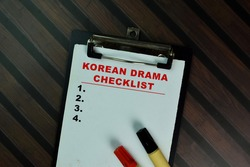 Korean Drama Checklist write on a paperwork and supported by additional services isolated on Wooden Table. Selective focus on Korean drama checklist text
