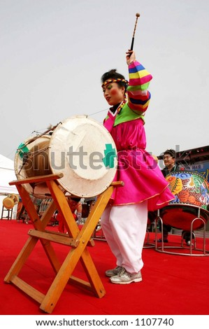 Korean drummer in traditional dress plays the drums at a festival in South Korea