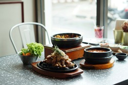 Korean food set on the table. Grilled pork belly served on hot stone, Korean mixed rice (Dolsot bibimbap), Kimchi Tofu Soup (kimchi jjigae), Most popular food in Korea.