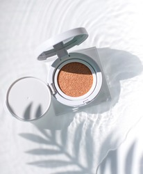 Korean foundation cushion with spf on the water surface under palm leaf shadow. Top view
