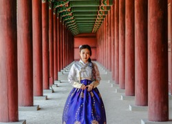 Korean girl in traditional dress, Hanbok at Korean traditional palace. Asian woman in Korean dress standing in temple or palace.
