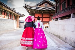 Korean Girls dressed Hanbok in traditional culture dress of South Korea walking in beautiful ancient castle architecture Gyeongbokgung Palace, People travel in Asia concept, Seoul City, South Korea.