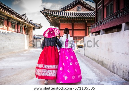 Korean Girls dressed Hanbok in traditional dress of south korea walking in Gyeongbokgung Palace, Seoul, South Korea. #571185535