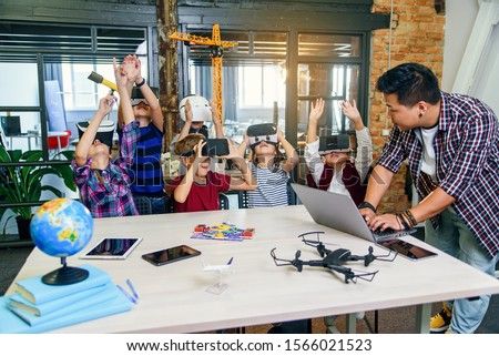 Korean male scientist with young pupils with laptop and VR headsets during a computer science class. Excited schoolchildren of smart modern school use virtual reality for studying new tecnologies. Foto stock ©