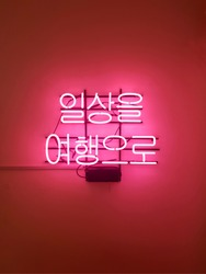 Korean neon sign stationary on the wall. 'Everyday as a trip.'