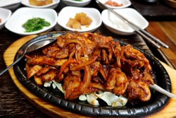 Korean Sizzling pork and squid with side dishes on wooden table
