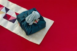 Korean traditional wrapping cloth made of silk(bojagi) and ornaments with copy space on red cloth background.