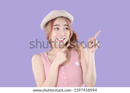 Korean woman point to special deals & discounts of promotions, tank top with beret hat, purple background
