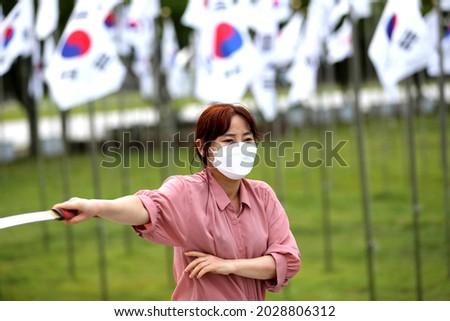 Korean woman practicing kendo in a hi-dong kendo pose with a sword Stock fotó ©