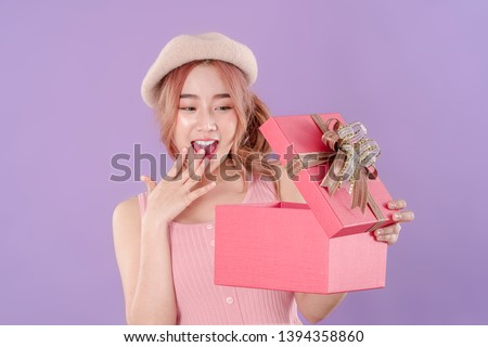 Korean woman surprised while opening the gift box, tank top clothing with hat, purple background