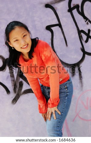 Korean woman wearing an orange top and jeans - graffiti wall