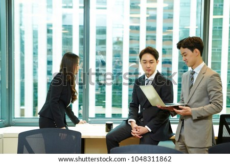 Korean workers looking at laptop screen