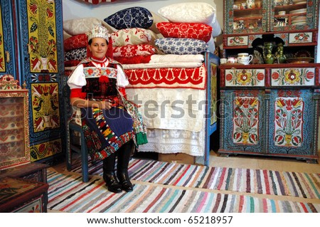 KOROSFO, ROMANIA - CIRCA MAY 2004: Girl wearing a traditional hungarian costume waits for visitors in a traditionally decorated room from the Korosfo area. Circa May, 2004 in Izvoru Crisului, Romania