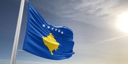 Kosovo national flag cloth fabric waving on beautiful sky.