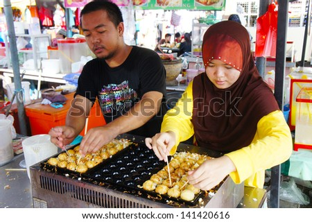 KOTA BHARU-JUNE 01: Two an unidentified street vendor prepares tokoyaki food on Wakaf Che Yeh on June 01, 2013 in Kota Bharu, Kelantan, Malaysia. Kelantan a haven for local food lovers