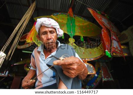 KOTA BHARU, MALAYSIA - APRIL 7 : The master kite maker, Shafie Bin Jusoh works on his craft in a small hut near the Cahaya Bulan Beach, April 7, 2009 in Kota Bharu, Malaysia