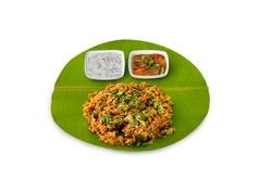 Kothu parotta, tamil nadu famous street food kothu parotta with chicken gravy and onion curd raita / onion pachadi, Curried Shredded Indian flat bread, veechu parotta served on banana leaf