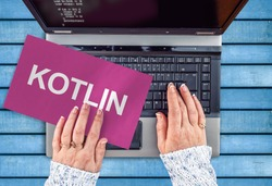 Kotlin mobile application programming language. Paper width word Kotlin and laptop,
