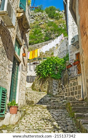 KOTOR, MONTENEGRO - JULY 12, 2014: Scenic mediterranean backstreet with the drying clothes and old narrow stairs, leading to the fortress of St John, on July 12 in Kotor.