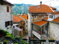 Kotor old town panoramic view, old houses with red tiling roof. Mountains background. Crna gora.