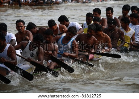 KOTTAYAM, INDIA - AUGUST 29 : Oarsmen in a snake boat team row vigorously in the Kottayam Boat race on August 29, 2010 in Kottayam, India.