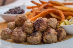 Kottbullar meatballs served with sweet potato fries, cucumber salad and lingonberry sauce