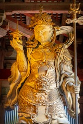 Koumokuten next to Great bronze Buddha known in Japanese as Daibutsu in Todaiji Temple, once one of the powerful Seven Great Temples. The buddha is 14.98m tall, and was completed in 751. Nara, Japan.